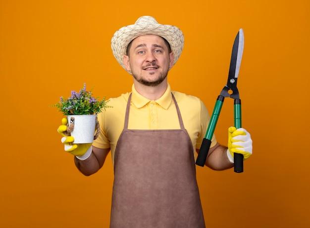 Jovem jardineiro vestindo macacão e chapéu segurando uma tesoura de sebes e um vaso de plantas olhando para a frente com uma cara feliz sorrindo em pé sobre a parede laranja Foto gratuita