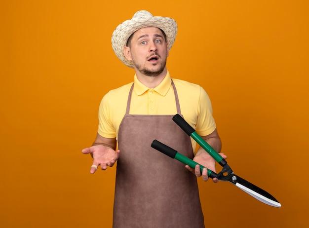 Jovem jardineiro vestindo macacão e chapéu segurando uma tesoura de sebes, olhando para a frente, confuso e descontente em pé sobre a parede laranja Foto gratuita
