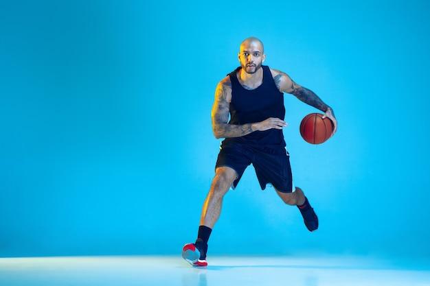 Jovem jogador de basquete da equipe vestindo treinamento sportwear, praticando em ação, movimento isolado sobre um fundo azul em luz de néon. conceito de esporte, movimento, energia e estilo de vida dinâmico e saudável. Foto gratuita