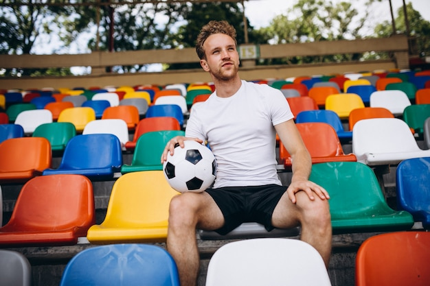 Jovem jogador de futebol em tribunas assistindo o jogo Foto gratuita