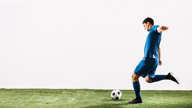 Jovem, jogador futebol, tiro bola Foto Premium