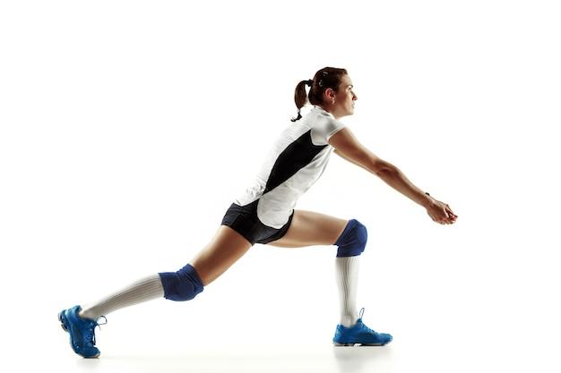 Jovem jogadora de vôlei isolada na parede branca. mulher em equipamentos de esporte e sapatos ou tênis, treinando e praticando. conceito de esporte, estilo de vida saudável, movimento e movimento. Foto gratuita