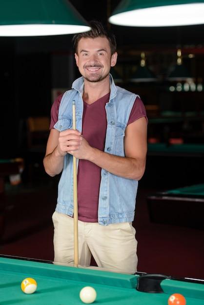 Jovem jogando bilhar no clube de bilhar escuro Foto Premium