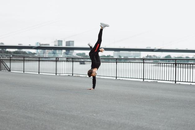 Jovem jogando esportes em uma cidade europeia. esportes em ambientes urbanos. Foto gratuita