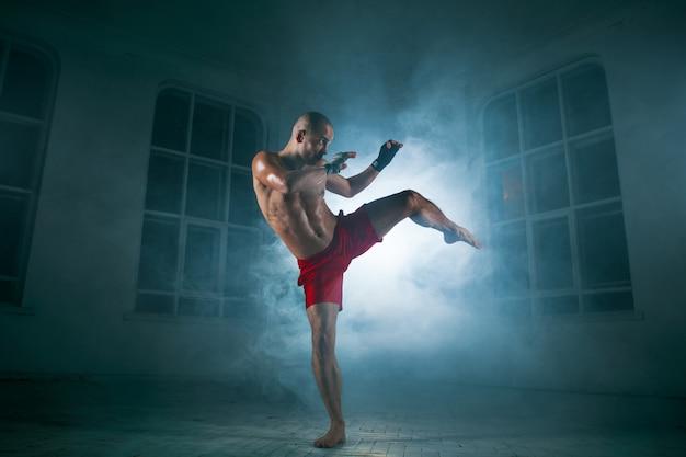 Jovem kickboxing na fumaça azul Foto gratuita
