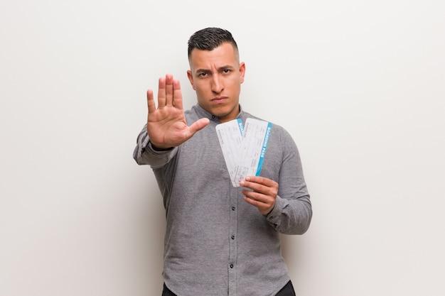 Jovem latina segurando uma passagem aérea, colocando a mão na frente Foto Premium