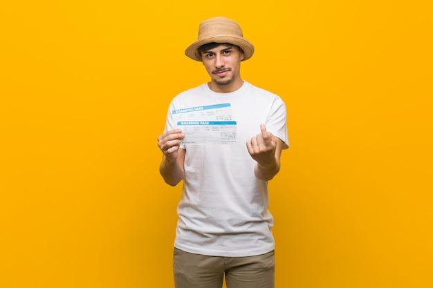 Jovem latino-americano segurando uma passagem aérea, apontando com o dedo para você como se estivesse convidando se aproximar. Foto Premium