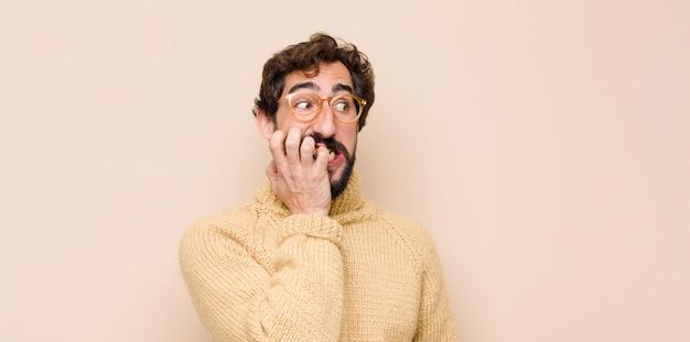 Jovem legal parecendo preocupado, ansioso, estressado e com medo, roendo as unhas e olhando para o espaço de cópia lateral na parede plana Foto Premium