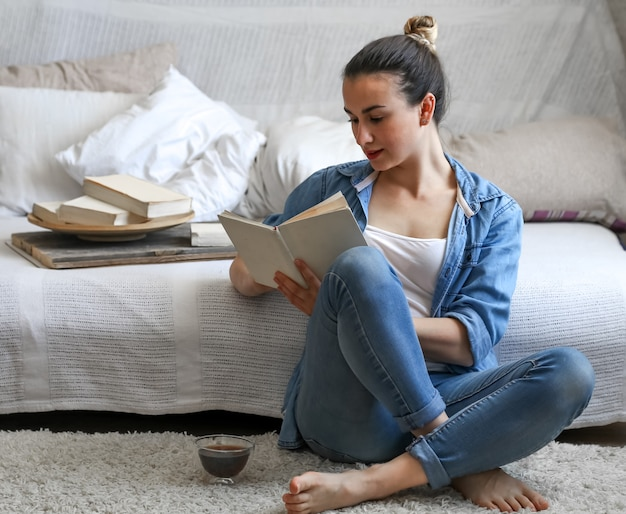 Jovem lendo um livro em uma sala aconchegante Foto gratuita