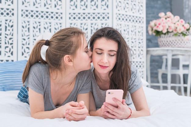 Jovem, lésbica, mulher, encontrar-se cama, beijando, para, dela, girlfriend's, pintinho, usando, telefone móvel Foto gratuita