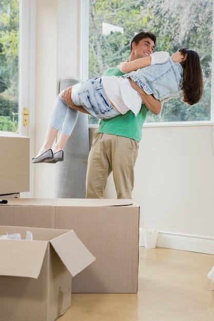Jovem, levantando a mulher nos braços enquanto desembalar caixas de papelão em casa nova Foto Premium