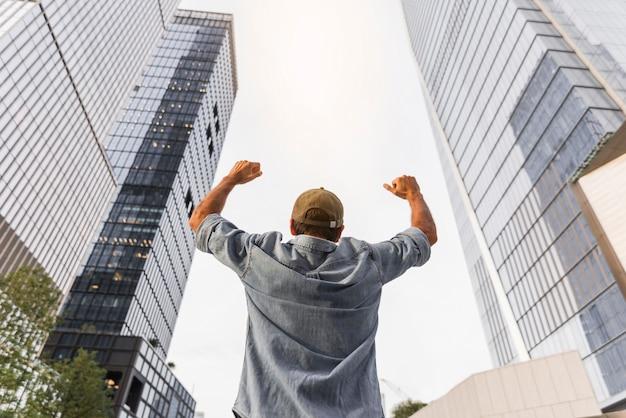 Jovem, levantando os punhos no ar Foto gratuita