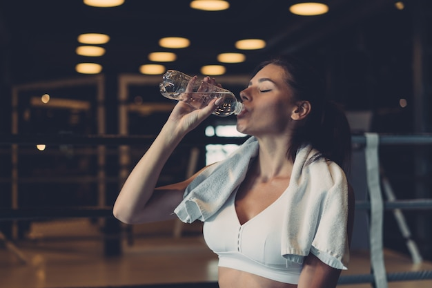 Jovem linda com uma toalha sobre os ombros, beber água de uma garrafa na academia Foto gratuita