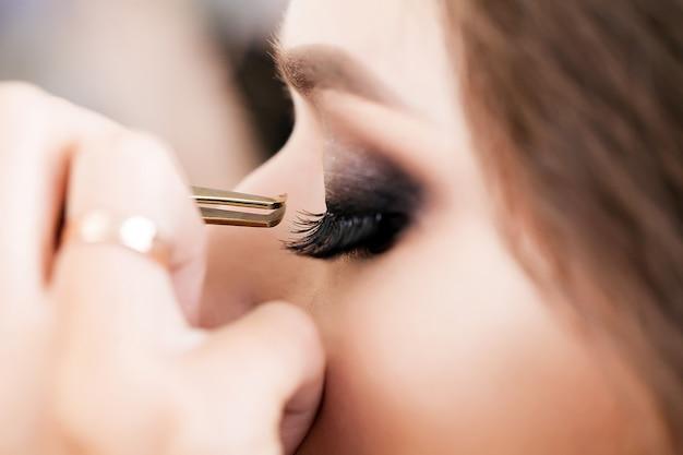Jovem, linda garota colocar maquiagem em um salão de beleza Foto Premium