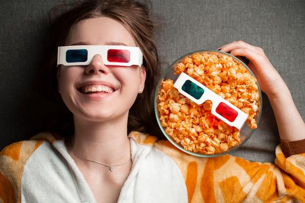 Jovem linda garota encontra-se sobre um fundo cinza em óculos 3d com pipoca Foto Premium