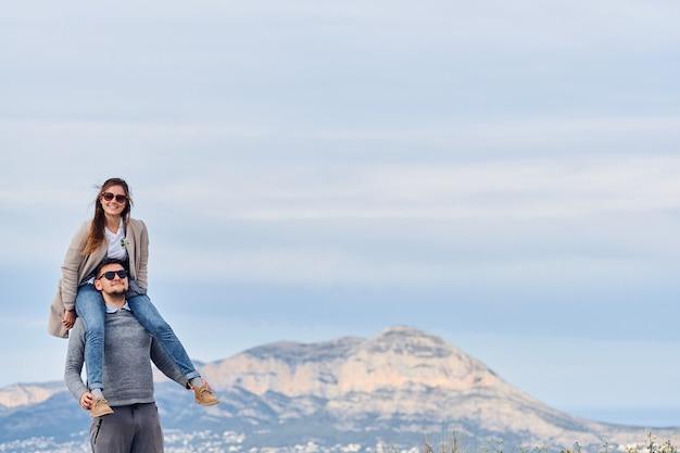 Jovem linda garota sentada nos ombros de seu namorado Foto Premium