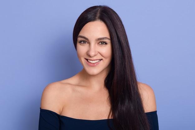 Jovem linda linda jovem com uma pele perfeita usando vestido azul escuro, posando com ombros nus Foto gratuita