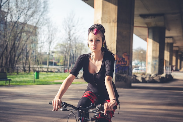 Jovem linda punk escuro garota andando de bicicleta | Foto Premium