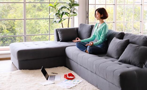 Jovem linda sentada no sofá e fazendo meditação Foto Premium