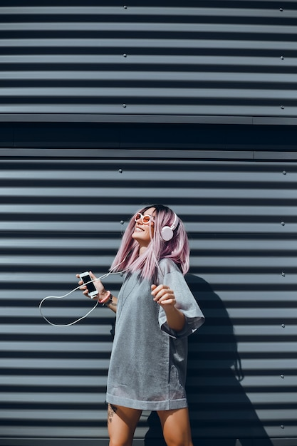 Jovem linda usa um smartphone na rua, navegar na internet e ouvir música Foto gratuita