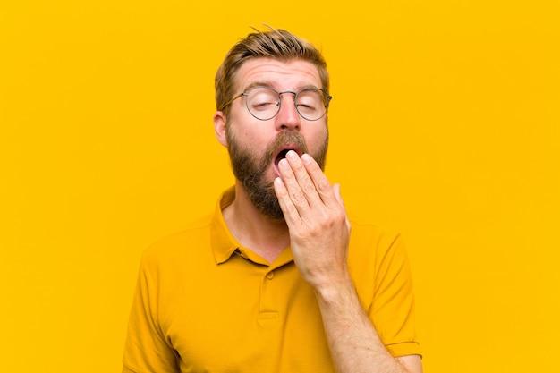 Jovem loira bocejando preguiçosamente de manhã cedo Foto Premium