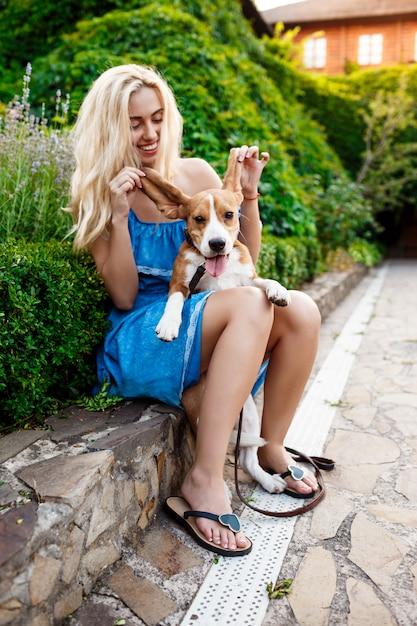 Jovem loira bonita andando, brincando com o cachorro beagle no parque. Foto gratuita