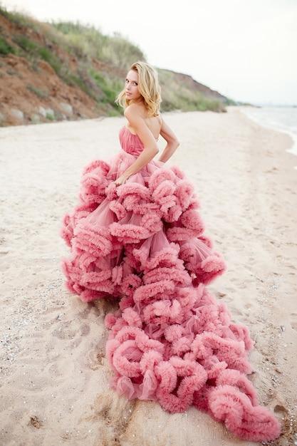 Jovem loira bonita com vestido rosa na praia Foto Premium