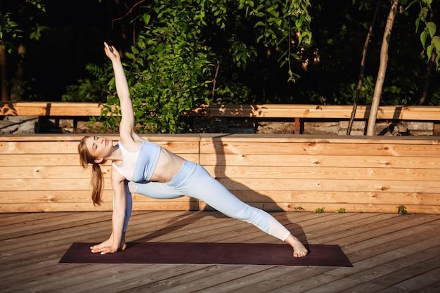 Jovem loira bonita praticando ioga fora ao nascer do sol. Foto gratuita