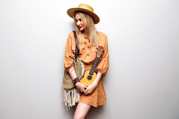 Jovem loira bonita segurando um ukulele com um vestido elegante boho e um chapéu de palha Foto gratuita