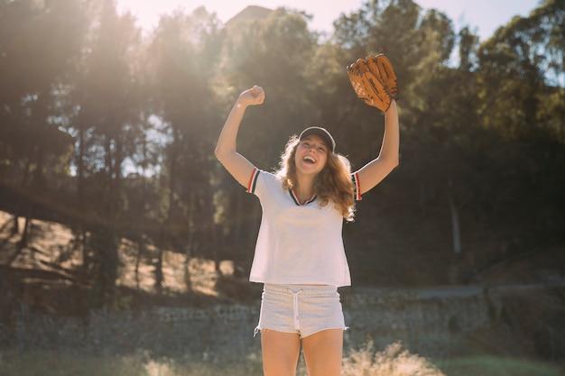 Jovem loira com as mãos levantadas e luva de beisebol no fundo da natureza Foto gratuita