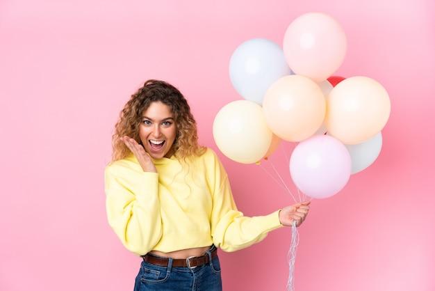 Jovem loira com cabelo encaracolado pegando muitos balões isolados na rosa com expressão facial surpresa Foto Premium