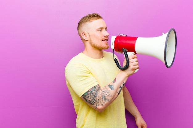 Jovem loira com um megafone, vestindo camiseta amarela contra fundo roxo Foto Premium