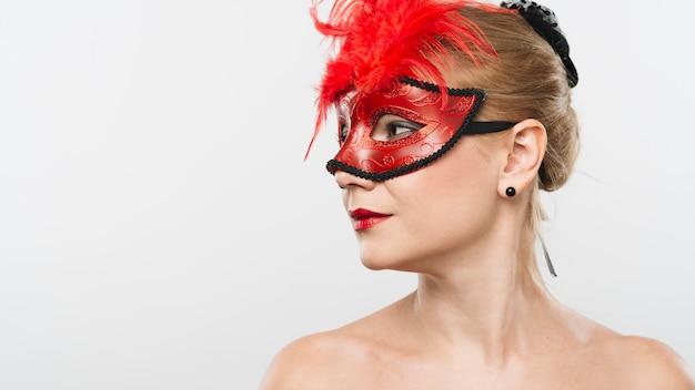 Jovem loira de máscara com penas vermelhas Foto gratuita