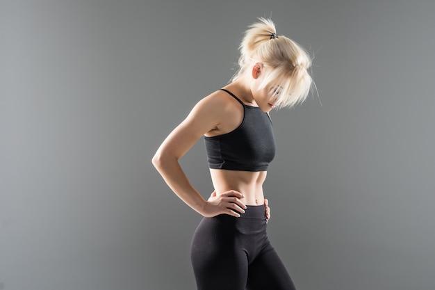 Jovem loira em forma de garota esportiva com roupas esportivas pretas demonstrando alongamento de corpo forte e musculoso Foto gratuita