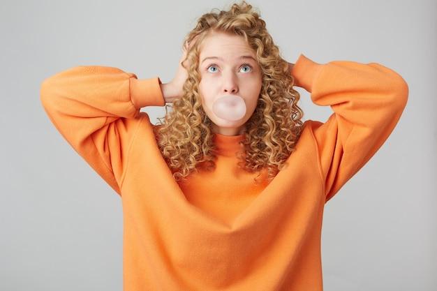 Jovem loira encaracolada vestida com um suéter laranja brilhante grande demais em pé com as mãos perto da cabeça Foto gratuita