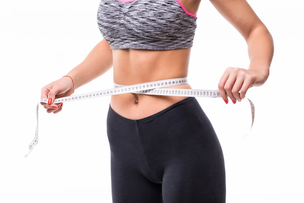 Jovem loira fitness mulher medindo seu corpo com uma régua vestida com roupas esportivas fasion para perder peso Foto gratuita