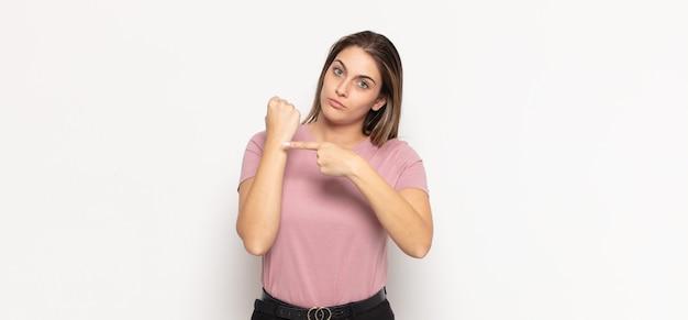 Jovem loira parecendo impaciente e zangada, apontando para o relógio, pedindo pontualidade, quer ser pontual Foto Premium