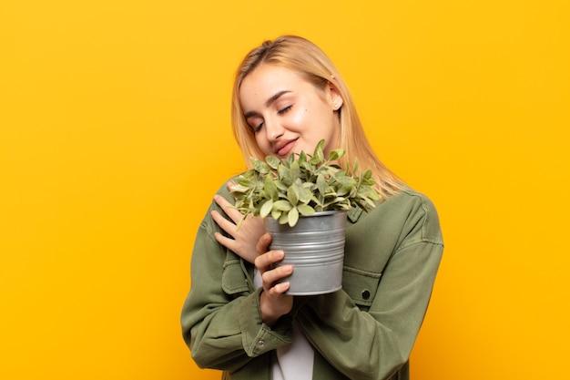 Jovem loira se sentindo apaixonada, sorrindo, se abraçando e se abraçando, permanecendo solteira, sendo egoísta e egocêntrica Foto Premium