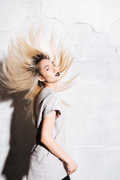 Jovem loira sensual dançando e sacudindo o cabelo Foto Premium