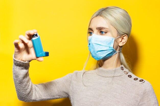 Jovem loira, usando máscara médica contra a gripe e suéter bege, segurando o inalador asmático na mão na parede amarela. Foto Premium