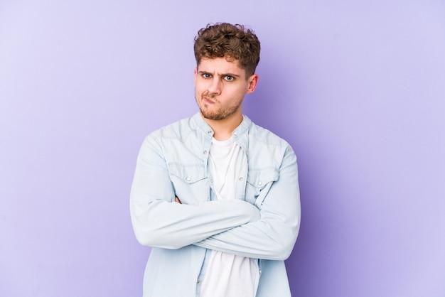 Jovem loiro encaracolado homem caucasiano isolado rosto carrancudo em desgosto, mantém os braços cruzados. Foto Premium