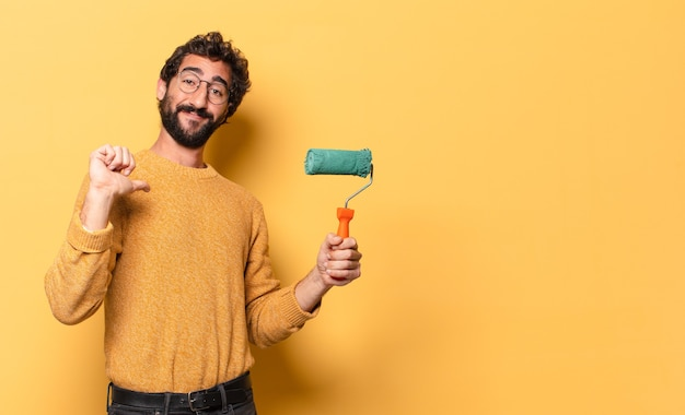 Jovem louco barbudo com um rolo de pintura pintando e mudando a cor da parede Foto Premium
