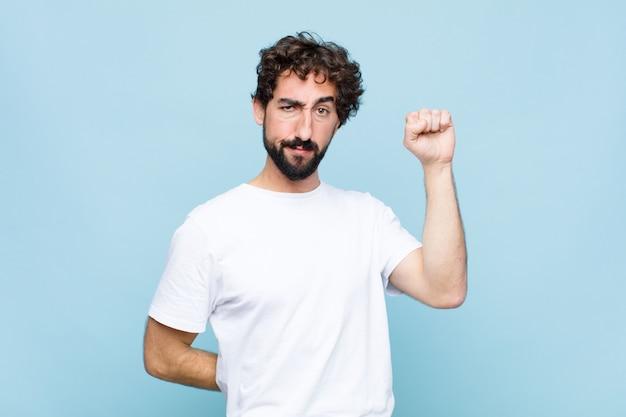 Jovem louco barbudo sentindo-se sério, forte e rebelde, levantando o punho, protestando ou lutando pela revolução em parede plana Foto Premium