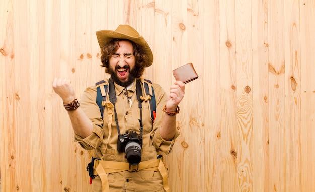 Jovem louco explorador com chapéu de palha e mochila em fundo de madeira Foto Premium