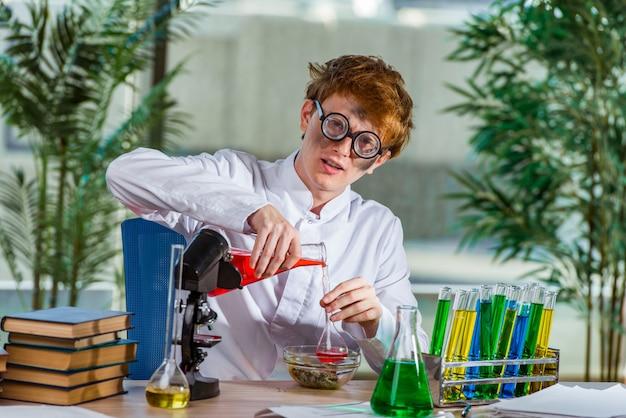 Jovem louco químico trabalhando no laboratório Foto Premium