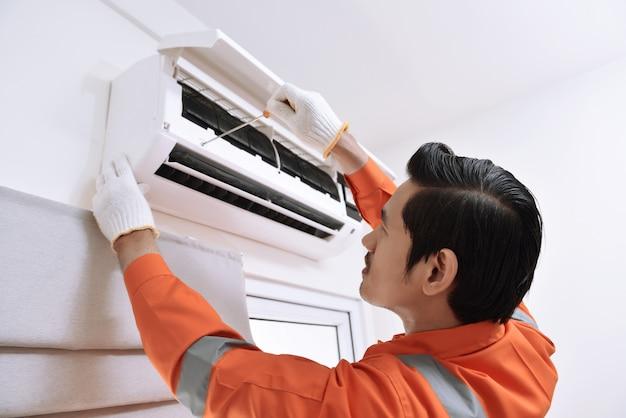 Jovem, macho asiático, técnico, reparar, ar condicionado, com, chave fenda Foto Premium