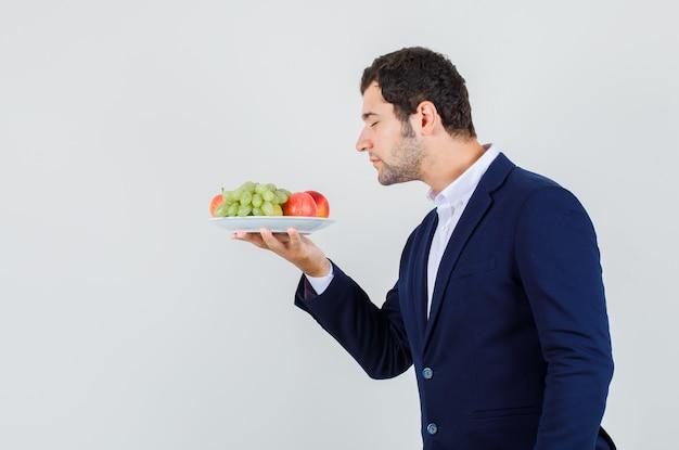 Jovem macho cheirando frutas frescas no prato de terno e parecendo em paz. . Foto gratuita