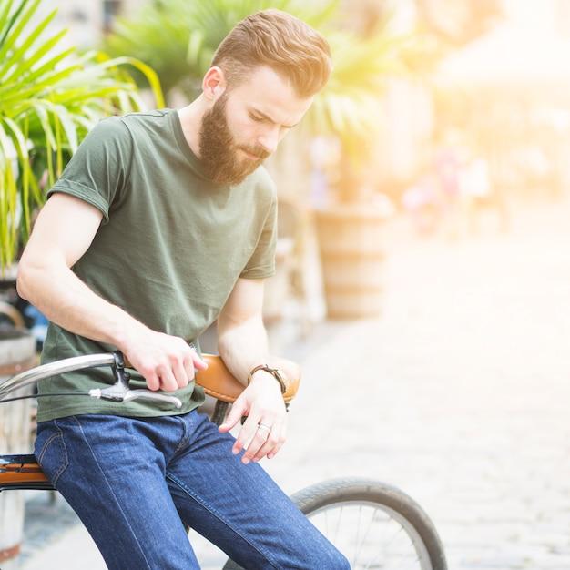 Jovem, macho, ciclista, sentando, ligado, seu, bicicleta Foto gratuita