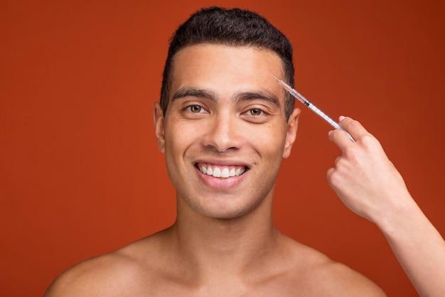 Jovem macho e seringa cheia de botox Foto gratuita