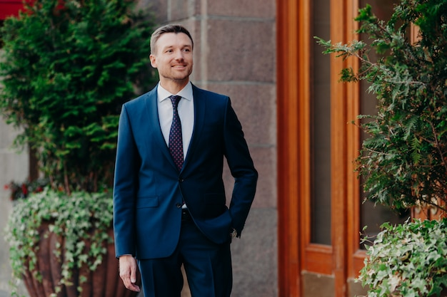 Jovem macho em roupa formal, fica perto de algum edifício, mantém a mão no bolso Foto Premium